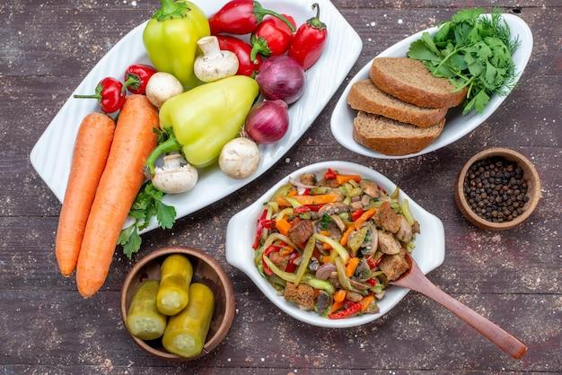 スライスした肉と調理した野菜、茶色の机の上のピクルスパン、フードミールディッシュミートのおいしいミートサラダの上面図