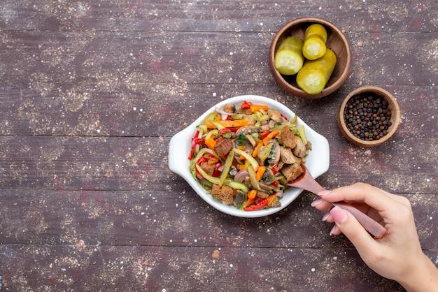 スライスした肉と調理した野菜のおいしいミートサラダと茶色の机の上のピクルス、フードミールディッシュミートの上面図