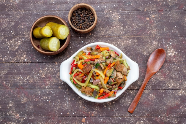 Вид сверху на вкусный мясной салат с нарезанным мясом и приготовленными овощами вместе с солеными огурцами на коричневом, мясное блюдо для еды