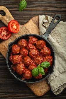 Вид сверху восхитительных фрикаделек с томатным соусом и свежим базиликом в чугунной деревенской старинной сковороде, которую подают на разделочной доске, деревянной предпосылке. вкусные домашние тефтели