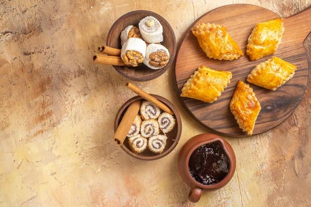 Вид сверху вкусных ореховых пирожных с конфитюрами на деревянной поверхности