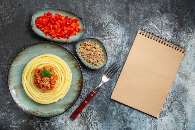夕食とフォークにトマトと肉を添えた青いプレートのおいしいパスタミールの上面図とその材料の横にある閉じたノート