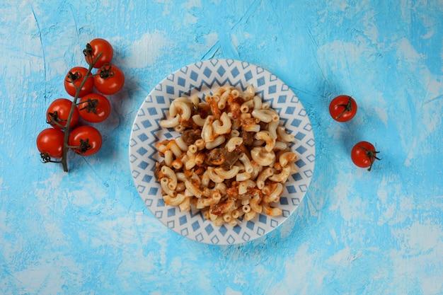 파란색 질감 된 테이블에 아름 다운 접시에 고기 조각과 소스와 함께 맛있는 파스타의 상위 뷰, 신선한 토마토 서빙을 장식. 공간을 복사하십시오.