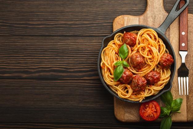 Взгляд сверху восхитительных макаронных изделий с фрикадельками, томатным соусом и свежим базиликом в чугунной деревенской винтажной кастрюле, служащей на разделочной доске, деревянной предпосылке. вкусные домашние спагетти с фрикадельками, место для текста