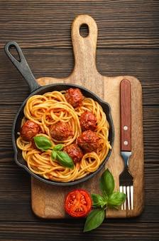 Взгляд сверху восхитительных макаронных изделий с фрикадельками, томатным соусом и свежим базиликом в чугунной деревенской винтажной кастрюле, служащей на разделочной доске, деревянной предпосылке. вкусные домашние спагетти с тефтелями