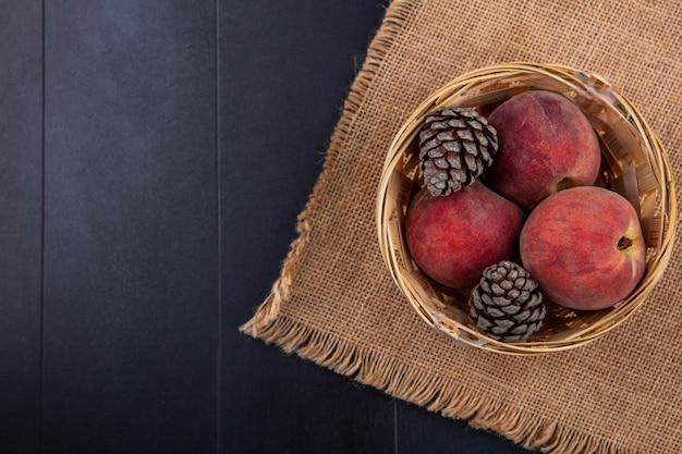 コピースペースと黒の袋の布のバケツに松ぼっくりとおいしい桃のトップビュー