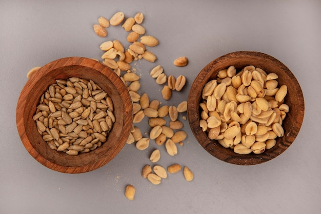 Вид сверху вкусных кедровых орехов на деревянной миске с очищенными семечками