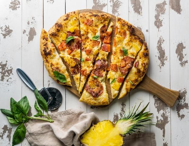 Вид сверху нарезанную кусочками вкусную пиццу с ананасом