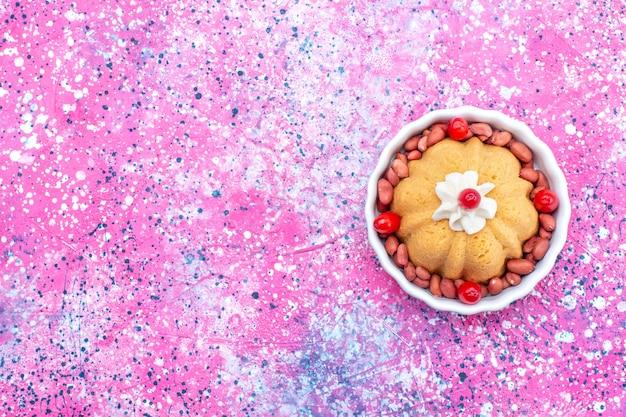 明るい机の上にクリームと新鮮なピーナッツ、ケーキビスケット甘い砂糖ナッツとおいしいプレーンケーキの上面図