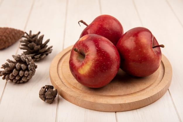 흰색 나무 표면에 고립 된 소나무 콘과 나무 주방 보드에 맛있는 빨간 사과의 상위 뷰