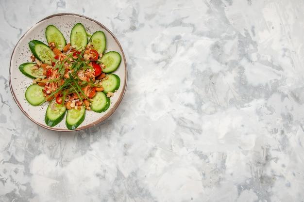キュウリのみじん切りと野菜を右側のステンドグラスの白い表面に飾ったおいしいサラダの上面図