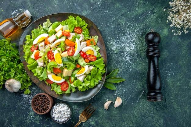 黒緑のミックス色の背景に多くの新鮮な食材スパイスニンニク落ちたオイルボトルの花とおいしいサラダの上面図