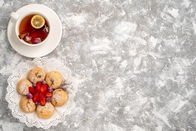 흰색 표면에 딸기와 차 한잔과 함께 맛있는 모래 쿠키의 상위 뷰