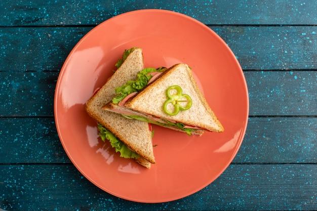Вид сверху вкусных бутербродов с зеленым салатом, ветчиной и помидорами