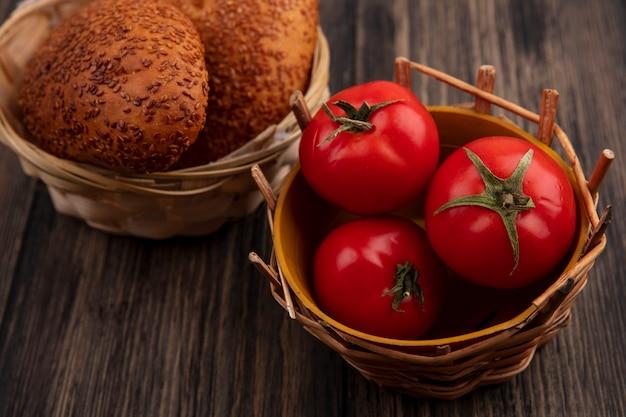 나무 배경에 양동이에 신선한 토마토와 양동이에 맛있는 참깨 버거의 상위 뷰