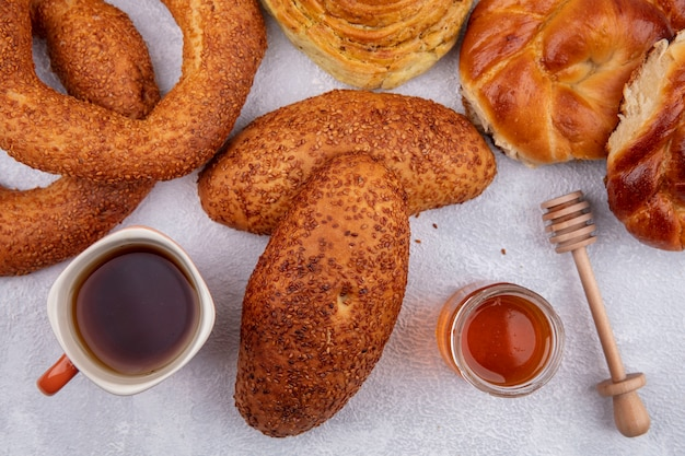 ガラスの瓶にお茶と蜂蜜のカップと白い背景で隔離のさまざまなパンとおいしいゴマのパテの上面図