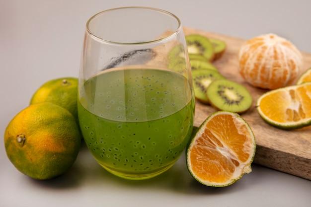 Вид сверху вкусного нарезанного киви с мандаринами на деревянной кухонной доске со свежим фруктовым соком