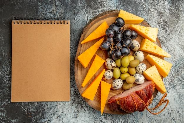 茶色のトレイに果物やワインの食べ物、灰色のテーブルにノートを含むおいしいスナックの上面図
