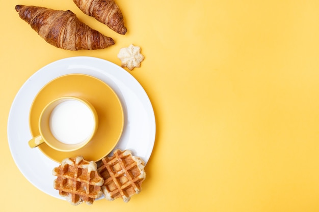 黄色の背景とコピー領域の右側にあるお菓子と牛乳のおいしいスナックの平面図