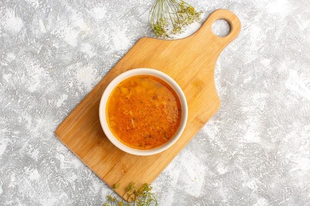 Вид сверху вкусного супа внутри тарелки на серо-светлой поверхности