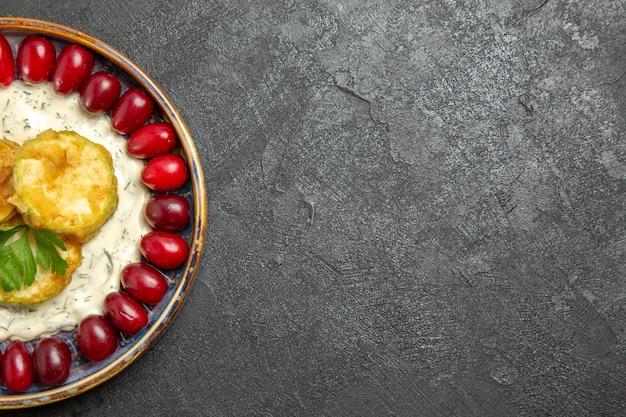 Вид сверху вкусной еды из кабачков со свежими красными кизилами на серой поверхности