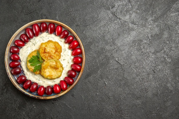 灰色の表面に新鮮な赤いハナミズキとおいしいスカッシュミールの上面図