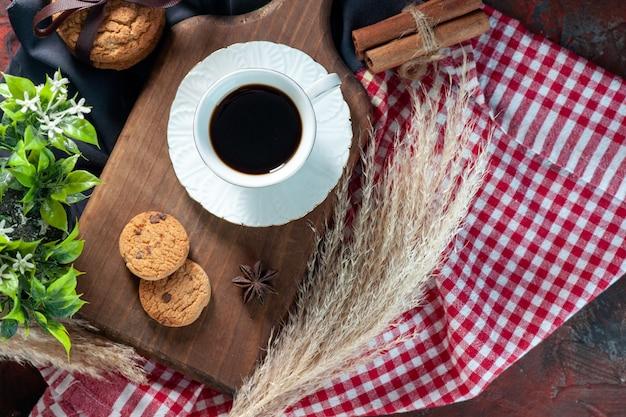 Вид сверху на вкусное сложенное печенье, перевязанное лентой на деревянной доске, и чашка кофе на деревянной доске, шипы, полотенца, цветок, корица, лайм на фоне темных цветов