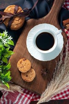 Вид сверху на вкусное сложенное печенье, перевязанное лентой на деревянной доске, и чашка кофе на деревянной доске, шипы, полотенца, цветок на фоне темных цветов
