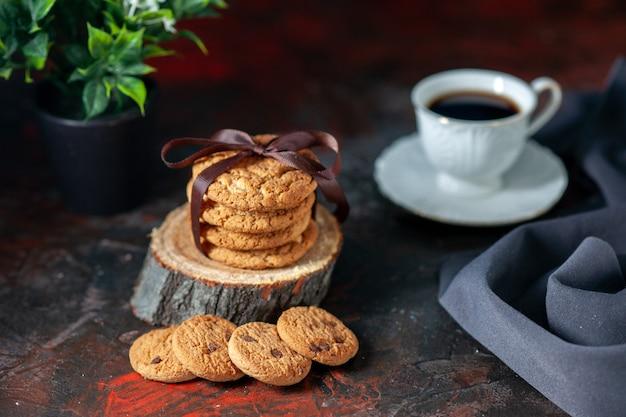 Вид сверху вкусного сложенного печенья, перевязанного лентой на деревянной доске, и чашка кофе в цветочном горшке на фоне темных цветов