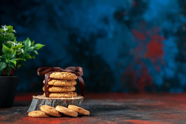 Вид сверху вкусного сложенного печенья, перевязанного лентой на деревянной доске и цветочного горшка на фоне темных цветов