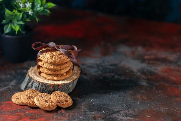 Вид сверху на вкусное сложенное печенье, перевязанное лентой на деревянной доске и цветочный горшок с правой стороны на фоне темных цветов