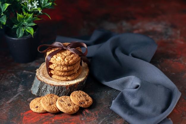 Вид сверху на вкусное сложенное печенье, перевязанное лентой на деревянной доске и полотенце для цветочного горшка на фоне темного микса цветов