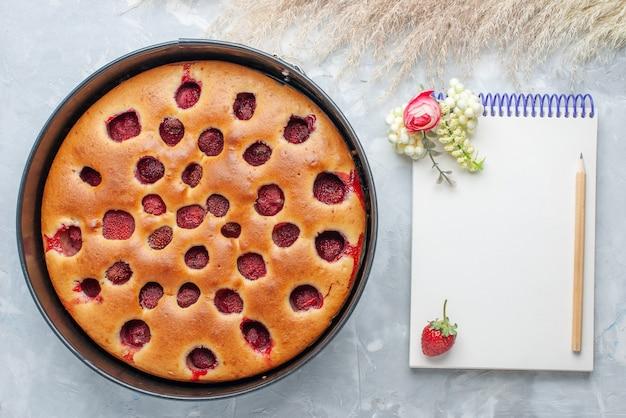 白い机の上に鍋とメモ帳で新鮮な赤いイチゴで焼いたおいしいストロベリーケーキの上面図、ケーキビスケットフルーツの甘い焼き