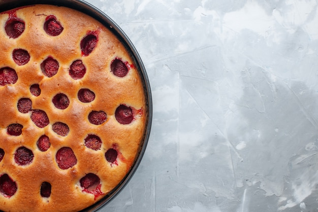Вид сверху на вкусный клубничный торт, запеченный со свежей красной клубникой внутри со сковородой на светлом столе, сладкое фруктовое печенье