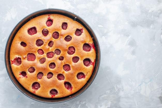 真っ白な机の上に鍋で新鮮な赤いイチゴで焼いたおいしいストロベリーケーキの上面図、ケーキビスケットフルーツ生地焼き