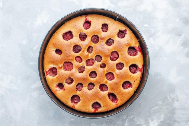 真っ白な机の上の鍋で新鮮な赤いイチゴで焼いたおいしいストロベリーケーキの上面図、ケーキビスケットフルーツ甘い生地焼き