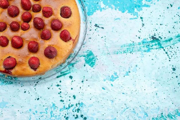 明るい机の上と内側に果物が丸い形をしたおいしいストロベリーケーキの上面図、ケーキ生地の甘いビスケットシュガー