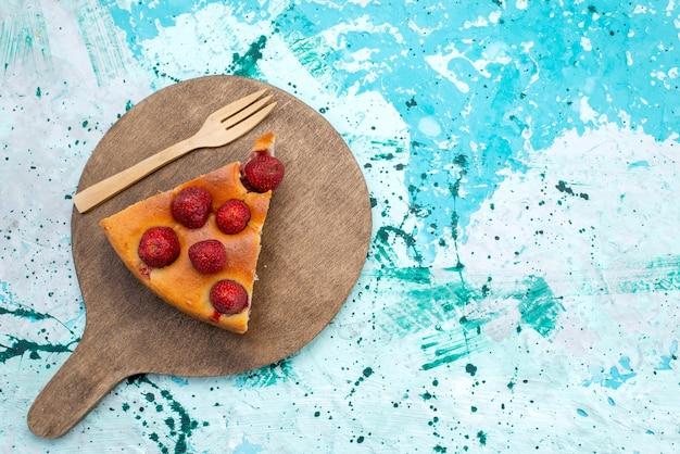 Вид сверху на вкусный клубничный торт, нарезанный ложкой, на ярко-синем, ягодном тесте для сладкой выпечки