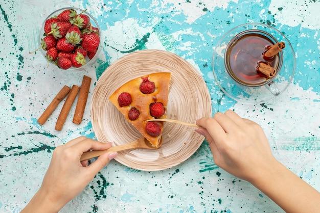 明るい青色の机の上でティーシナモンと新鮮な赤いイチゴと一緒に食べられるおいしいストロベリーケーキスライスしたおいしいケーキの上面図、ケーキ焼き生地甘い