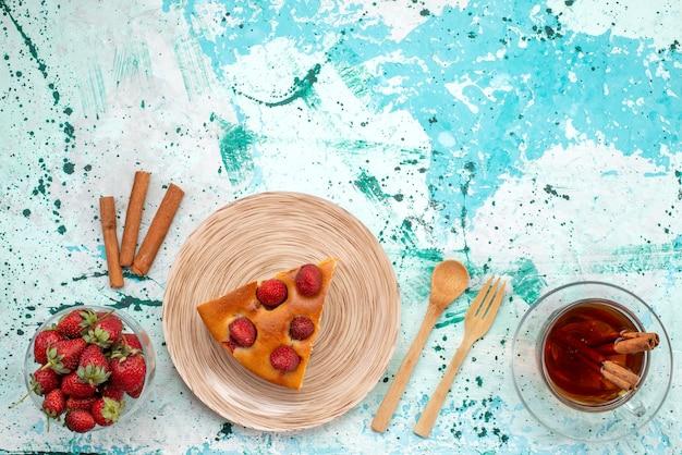 明るい青色の机の上にティーシナモンと新鮮な赤いイチゴ、ベリーケーキ焼き生地とおいしいストロベリーケーキスライスしたおいしいケーキの上面図