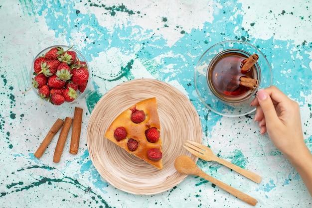 明るい青色の机の上にティーシナモンと新鮮な赤いイチゴ、ケーキ焼き生地甘い砂糖とおいしいストロベリーケーキスライスしたおいしいケーキの上面図