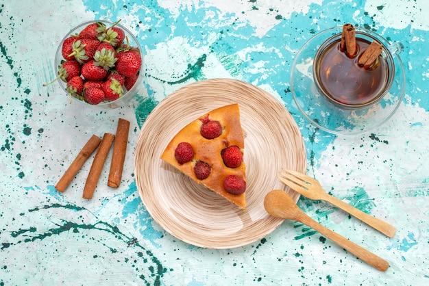 明るい青色の机の上にお茶シナモンの新鮮な赤いイチゴとおいしいストロベリーケーキスライスしたおいしいケーキの上面図、ケーキ焼き生地甘い