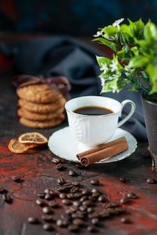 Вид сверху вкусного сахарного печенья и чашки кофейных зерен цветочный горшок полотенце с корицей и лаймом на фоне темных цветов