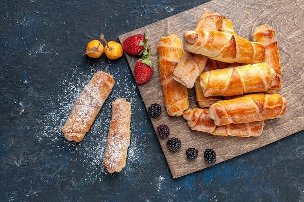 Вид сверху на восхитительные сладкие браслеты с начинкой, запеченные с фруктами на темном, выпеченном бисквитном сахарном сладком десерте