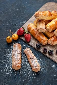Вид сверху на восхитительные сладкие браслеты с начинкой, вкуснятина, запеченная с фруктами на темном полу, выпечка торта бисквитного сахара сладкого десерта
