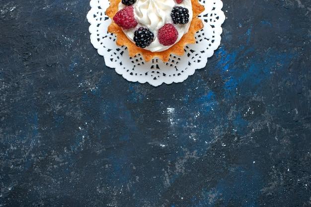Вид сверху вкусного сладкого торта с разными ягодами и сливками на темно-сером столе, бисквитный торт цвета ягод фруктов