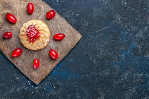 ダークグレーの机の上に赤いハナミズキ、フルーツベリー色のケーキビスケットとおいしい甘いケーキの上面図
