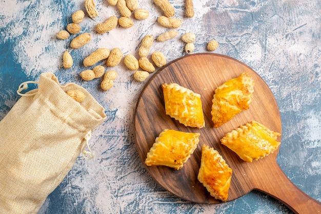 青い表面にピーナッツが付いているおいしい甘いペストリーの上面図