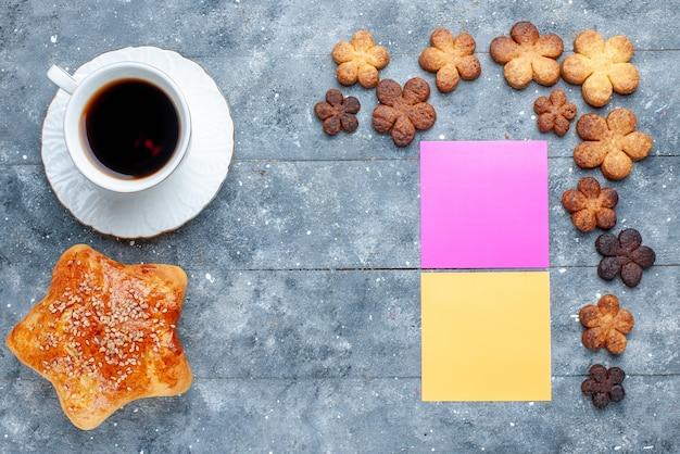 灰色の机の上にクッキーコーヒー、甘い焼き菓子ケーキで形作られたおいしい甘いペストリースターの上面図
