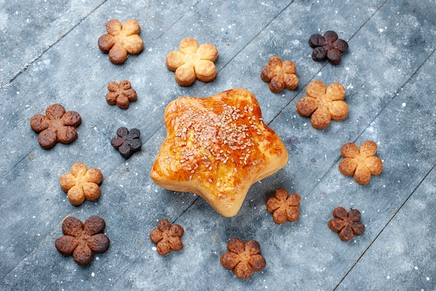 灰色の甘い焼き菓子ケーキにクッキーで形作られたおいしい甘いペストリースターの上面図